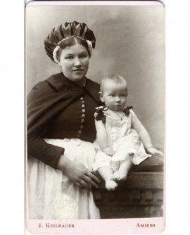 Nourrice en cape, tablier blanc et coiffe bouffante présentant un enfant