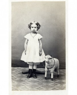 Fillette en robe blanche tenant un mouton à roulettes (jouet)