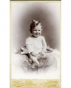 Bébé souriant assis sur une peau de mouton