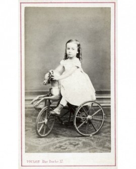 Fillette en robe blanche sur un cheval de bois tricycle (jouet)