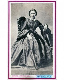 Femme en robe assise appuyée sur une chaise