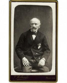 Homme chauve et moustachu âgé assis, arborant deux médailles