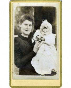 Femme debout tenant un bébé en robe de baptême