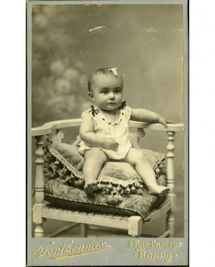 Bébé en chemise assis sur un coussin