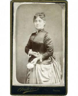 Femme en robe à tournure debout, une fleur à la main