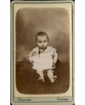Bébé en chemsie, épaule dénudée, assis sur un coussin