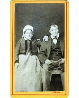 Couple âgé assis, homme son chapeau à la main, femme en coiffe