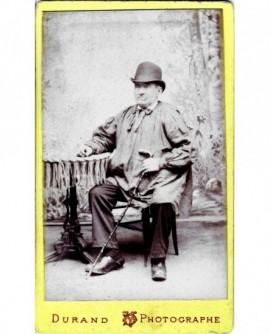 Homme assis en blaude et en melon, canne à la main