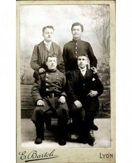 Groupe de quatre hommes, deux assis et deux debout la main sur l'épaule des premiers