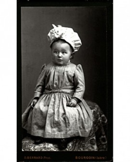 Bébé, coiffé d'un large bonnet, assis sur un tapis posé sur un siège.