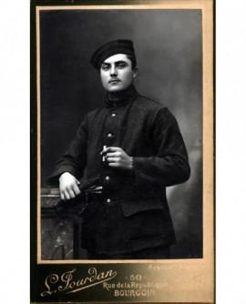 Militaire en cheiche debout, gants et cigarette à la main