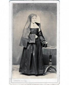 Religieuse debout, tenant un livre sur la tranche posé sur une table