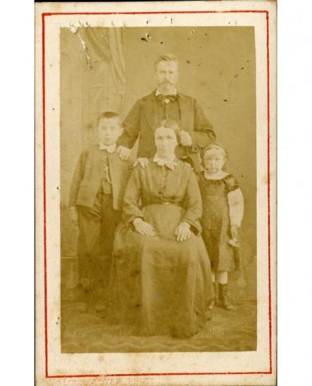 Portrait de famille: mère assise, père debout derrière et deux enfants