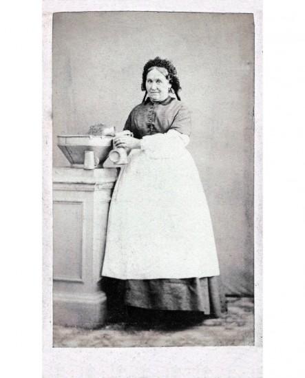 Femme en tablier blanc près d'instruments de cuisine (cuisinière)