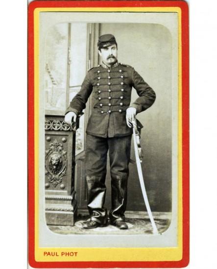 Militaire du 21è (hussards) en képi et bottes tenant son sabre