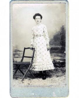 Jeune fille en robe à fleurs debout appuyée à une chaise
