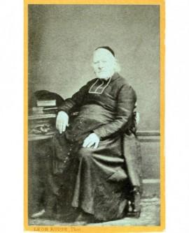 Ecclésiastique en calotte et rabat assis à une table