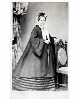 Femme en manteau et capot debout, une ombrelel à la main, appuyée sur une chaise