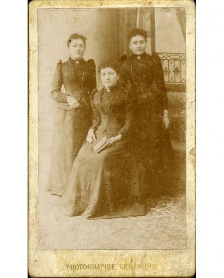Trois soeurs? une assise avec livre, les deux autres debout