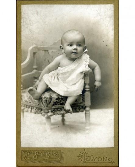 Bébé en chemise, épaule dénudée, assis sur une petite chaise
