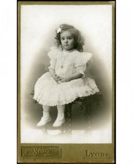 Petite fille en robe blanche assise