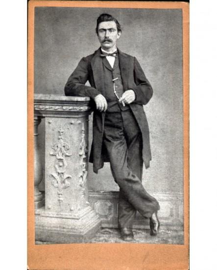 Homme moustachu accoudé à une stèle sculptée