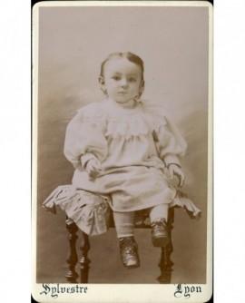 Bébé en robe et en souliers assis sur un tabouret