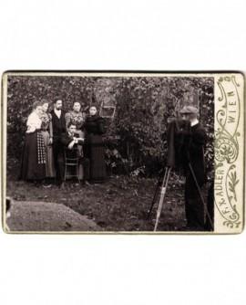 Photographe au travail, prenant un groupe familial dans un jardin