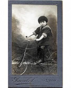 Enfant en col marin sur un vélo. tricycle jouet