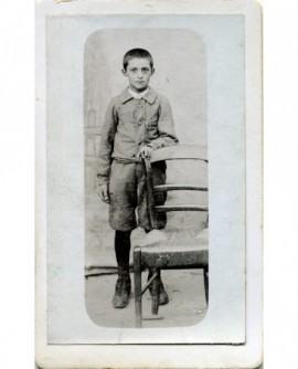 Enfant debout tenant une chaise