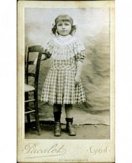 Petite fille en robe Vichy à carreaux appuyée sur une chaise