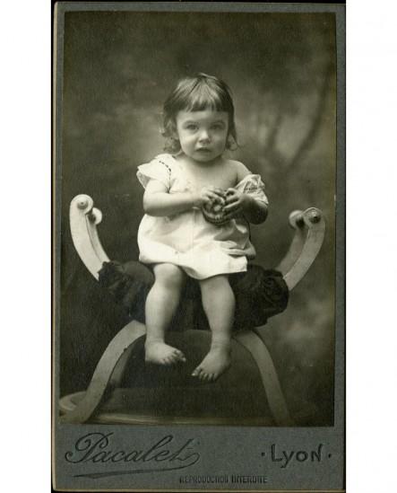Bébé en chemise, épaule dénudée, assis sur une chaise