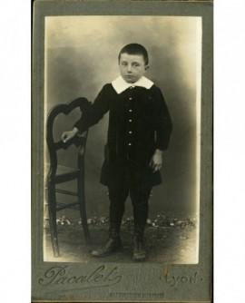 Petit garçon debout, se tenant à une chaise