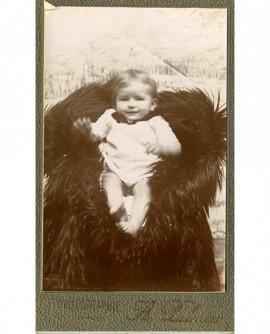 Bébé en chemise, assis sur un fauteuil recouvert d'une peau de bête
