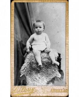 Bébé torse nu, assis sur une peau de mouton