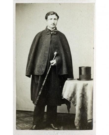 Homme en houppelande, canne à pommeau en main, chapeau posé