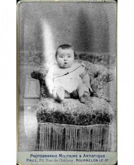 Bébé en chemise, épaule dénudée, assis sur un fauteuil