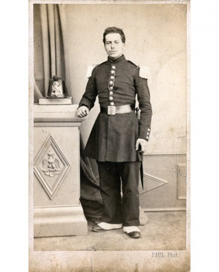 Militaire baionnette au côté, shako posé sur une console