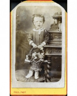 Petite fille debout sur une chaise, tenant un panier