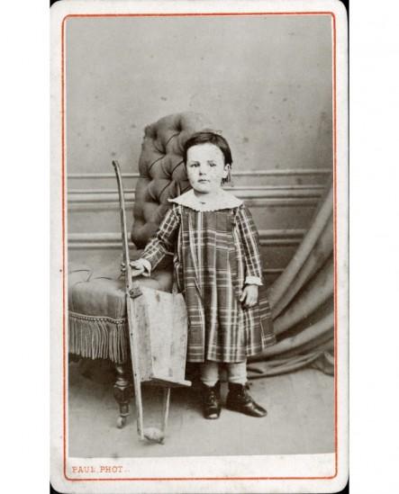 Petite fille debout avec petite brouette en bois (jouet)