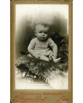 Bébé en chemise, épaule dénudée, assis sur un coussin
