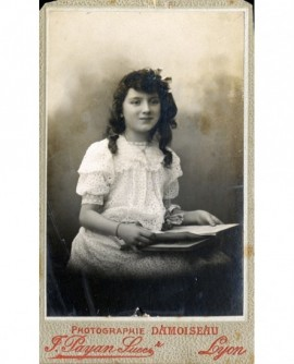 Fillette en robe blanche tenant un livre ouvert (Suzanne Peuch)