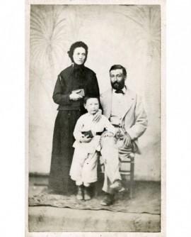 Famille: père assis, mère et fils debout, chacun avec un livre