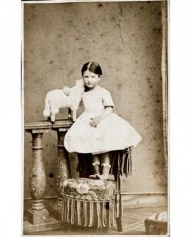 Fillette en robe blanche sur une chaise. mouton à roulettes (jouet)