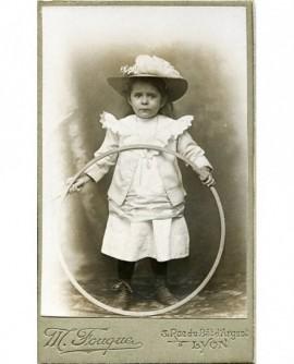 Enfant avec chapeau tenant un cerceau (jouet)