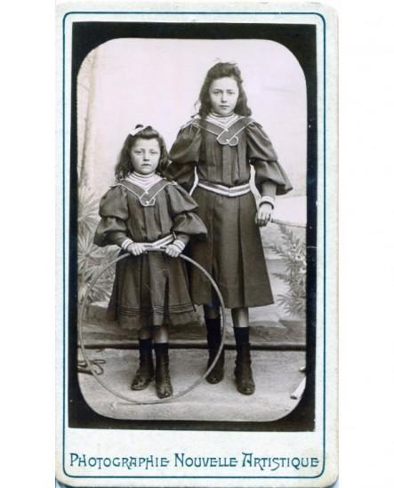 Deux fillette en robe et veste de maron, avec cerceau (jouet)
