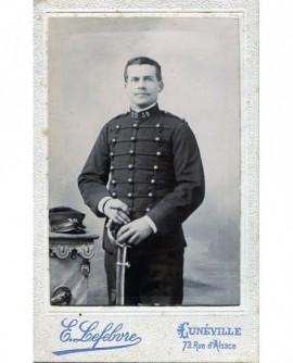 Jeune garçon debout en costume tenant une casquette
