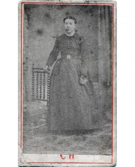 Femme posant debout appuyée sur une chaise