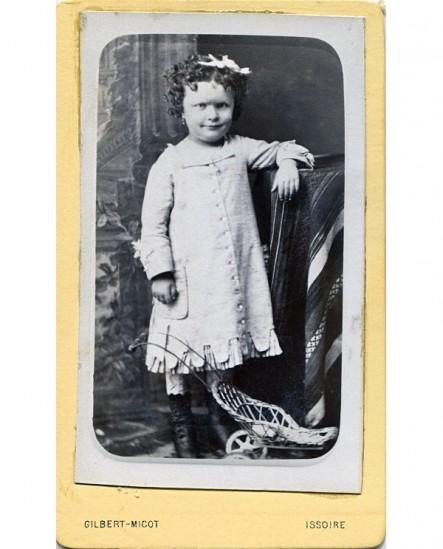 Enfant en robe posant debout devant un jouet