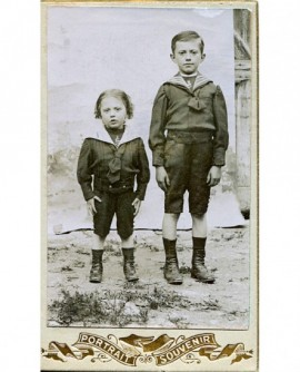 Jeunes garçons en veste marin posant devant un drap en extérieur